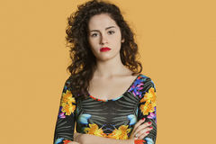 Portrait of a confident young woman with arms crossed over colored background Stock Image