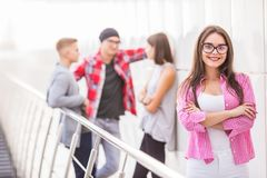 Portrait of confident young woman with group of people talking in background royalty free stock photo