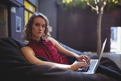 Portrait of confident young woman sitting with laptop on bean bag. Against wall Royalty Free Stock Images