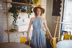 Portrait of confident young woman standing at coffee shop royalty free stock image