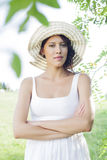 Portrait of confident young woman in sundress and hat standing arms crossed in park Stock Photos
