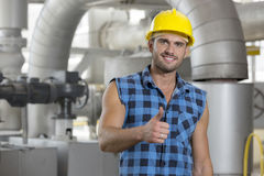 Portrait of confident young worker gesturing thumbs up in industry Royalty Free Stock Photo