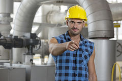 Portrait of confident young worker pointing at you in industry Royalty Free Stock Image