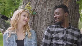 Portrait confidient pretty blond woman and handsome African American man talking sitting under an old tree in the park. Pretty blond woman and handsome African stock video