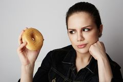Portrait of a confused beatiful caucasian woman thinking to eat donut or not isolated over white background. stock image