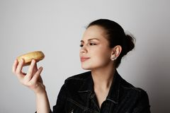 Portrait of a confused beatiful caucasian woman thinking to eat donut or not isolated over white background. stock images