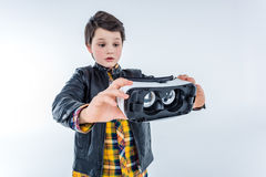 Portrait of confused boy holding virtual reality headset Stock Images