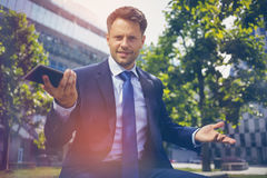 Portrait of confused businessman holding mobile phone Royalty Free Stock Photo