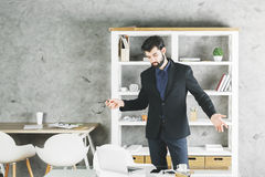 Portrait of confused businessman. Portrait of confused young businessman looking at desk with laptop and other items in modern office Royalty Free Stock Images