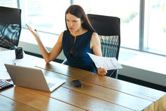 Portrait of a Confused Businesswoman which Works With Papers in Stock Image