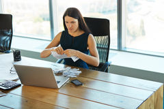 Portrait of a Confused Businesswoman which Works With Papers in. Office Stock Photo