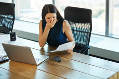 Portrait of a Confused Businesswoman which Works With Papers in. Office Royalty Free Stock Photography