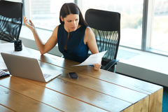 Portrait of a Confused Businesswoman which Works With Papers in. Office Royalty Free Stock Image