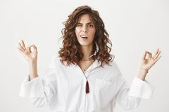 Portrait of confused cute caucasian woman with trendy haircut standing in meditating pose with raised hands and zen. Gesture, peeking at camera with clueless Royalty Free Stock Photos