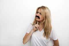 Portrait of confused in fake mustache against white background Royalty Free Stock Photography
