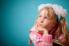 Portrait of confused girl holding two books. Girl slightly puzzlement. on blue background Royalty Free Stock Photos