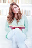 Portrait of confused lovely woman reading a book in her living r Royalty Free Stock Photos