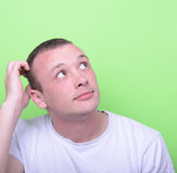 Portrait of confused man against green background looking up Stock Image