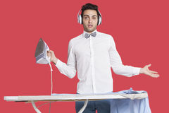 Portrait of a confused man in formals ironing as he listens to music over red background Stock Photography