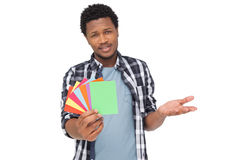 Portrait of a confused man holding colorful papers Stock Photography