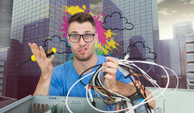 Portrait of confused it professional with screw driver and cables in front of ope Royalty Free Stock Photography