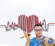 Portrait of confused it professional with screw driver and cables in front of ope Royalty Free Stock Photo
