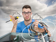 Portrait of confused it professional with screw driver and cables in front of ope Royalty Free Stock Photos
