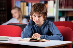 Portrait Of Confused Schoolboy. Portrait of cute little schoolboy reading book while sitting at table in library Stock Photography