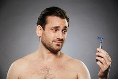 Portrait of a confused shirtless man looking at razor. Isolated over gray background royalty free stock images