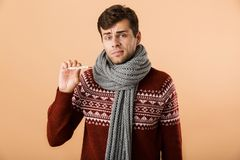 Portrait of a confused sick young man dressed in sweater. And scarf isolated over beige background, showing thermometer royalty free stock photography
