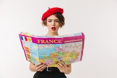 Portrait of a confused woman wearing red beret. Reading travel map guide isolated over white background Stock Photography