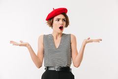 Portrait of a confused woman wearing red beret. Shrugging shoulders isolated over white background Stock Images