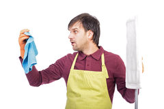 Portrait of confused young man with apron and cleaning equipment Stock Photo