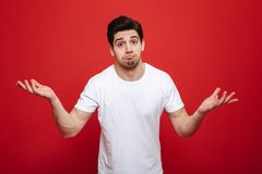 Portrait of a confused young man in white t-shirt. Shrugging shoulders isolated over red background Stock Image