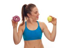 Sportive woman choosing between donut and apple stock images