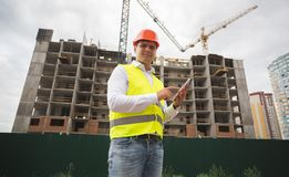 Portrait of construction engineer in hardhet using digital tablet on building site royalty free stock images