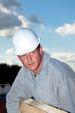 Portrait construction worker. Builder at work with wooden  roof construction Stock Photo
