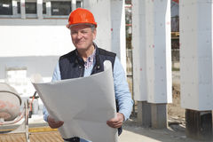 Portrait of construction worker. Construction worker holding at set of building plans on the construction site. Small business Royalty Free Stock Photo