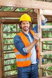 Portrait Of Construction Worker Measuring Timber Stock Photography
