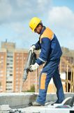 Portrait of construction worker with perforator. Portarait of positive Builder worker with pneumatic hammer drill equipmant at construction site Stock Images