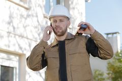 Portrait contractor outdoors using telephone spirit level on shoulder stock photography