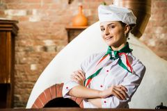 Portrait of a cook. Is on the traditional kitchen, crossed her arms Royalty Free Stock Photos