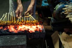 Portrait of a cook hand`s grill a sate on the folding grill shelf. With fire on charcoal royalty free stock photos