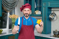 Portrait of cook with knife and orange pepper. Man prepares knife and paprika in hands on kitchen. Professional Chef at kitchen royalty free stock photos
