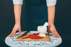 Portrait of a cook. Preparing food with cooking mortar  on black background Royalty Free Stock Image