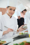 Portrait of a cooking apprentice preparing dish Stock Photography