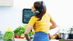 Portrait of cooking woman in kitchen. Girl standing back. With listening music Royalty Free Stock Images