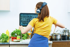 Portrait of cooking woman in kitchen. Girl standing back Royalty Free Stock Photos