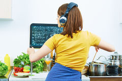 Portrait of cooking woman in kitchen. Girl standing back Royalty Free Stock Image