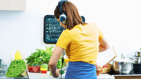 Portrait of cooking woman in kitchen. Girl standing back